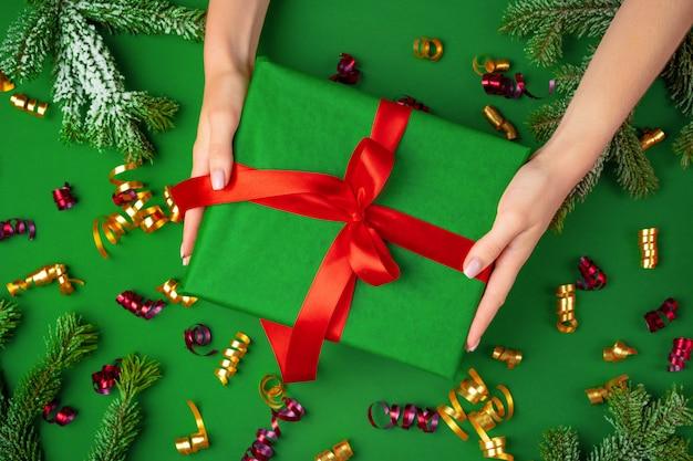 Mains tenant un cadeau de noël sur fond vert