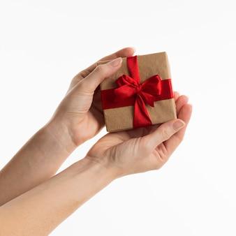Mains tenant un cadeau avec ruban et arc