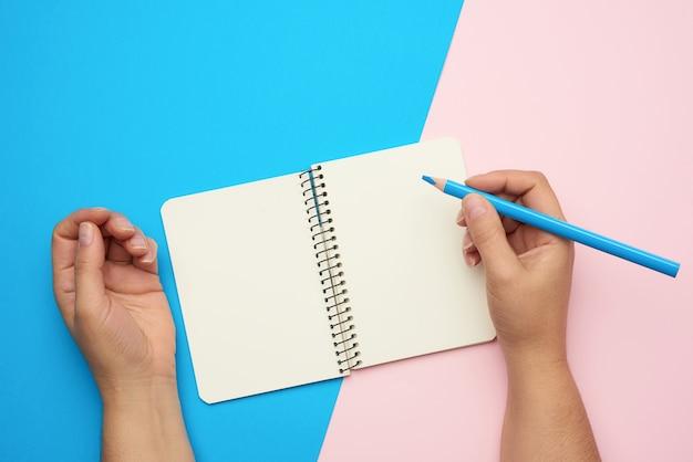 Mains tenant un cahier ouvert avec des feuilles blanches vides