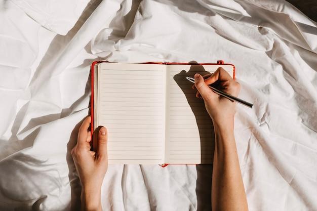 Mains tenant un cahier vierge ouvert et un stylo sur le lit