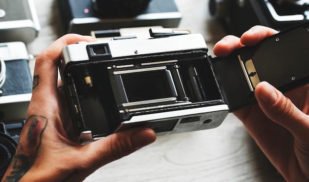 Mains tenant une caméra ouverte