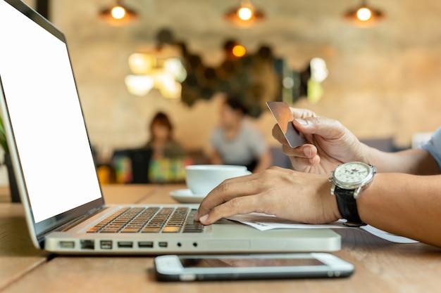 Mains tenant la carte de crédit et à l'aide du clavier portable sur la table.