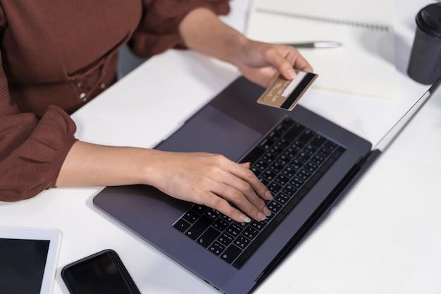 Mains tenant une carte de crédit et utilisant un ordinateur portable pour faire du shopping en ligne