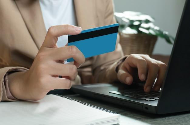 Mains tenant une carte de crédit et utilisant un ordinateur portable. shopping en ligne. travail à domicile concept