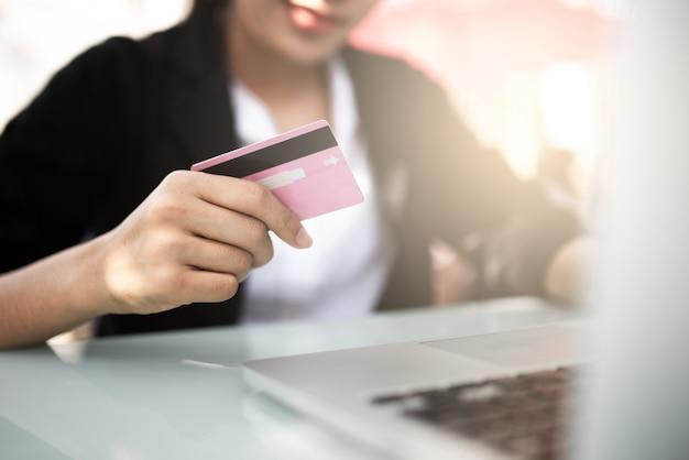 Mains tenant une carte de crédit et utilisant un ordinateur portable.