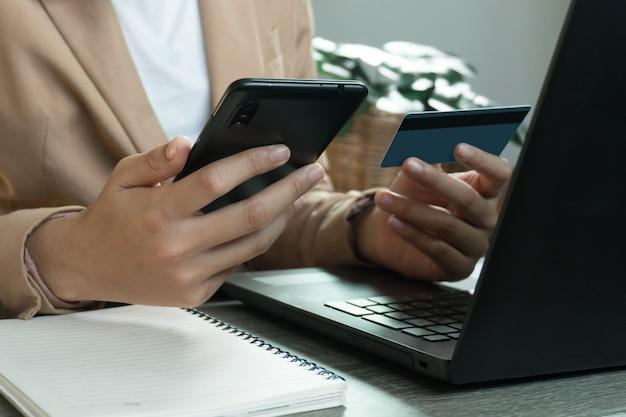 Mains tenant la carte de crédit et utilisant le téléphone et l'ordinateur portable. achats en ligne concept de travail à domicile