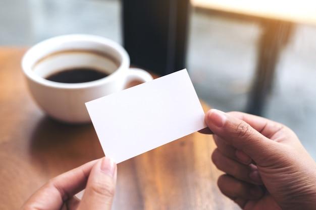 Mains tenant une carte de visite vide avec une tasse de café sur la table