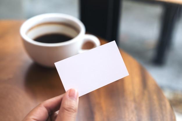 Mains tenant une carte de visite vide et une tasse de café