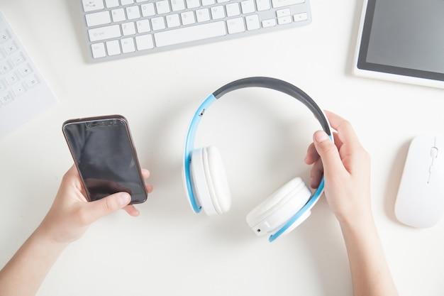 Mains tenant un casque et un smartphone