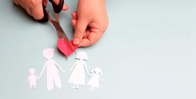 Mains tenant des ciseaux coupe papier familial sur fond bleu.