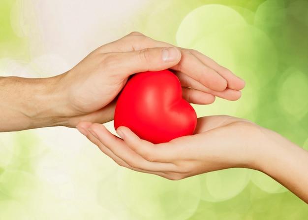 Mains tenant le coeur décoratif rouge