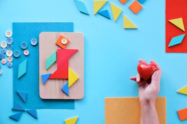 Mains tenant le coeur de pierre rouge. conception créative pour le 2 avril, journée mondiale de sensibilisation à l'autisme