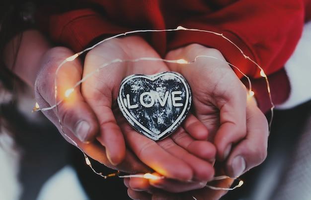 Mains tenant le coeur de pierre avec texte d'amour.