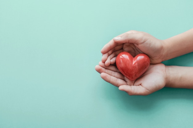 Mains tenant un coeur rouge sur fond bleu