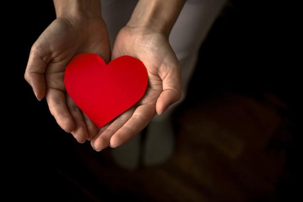 Mains tenant coeur rouge sur fond noir. assurance maladie, jour du don d'organes, concept caritatif. concept de journées mondiales de la santé, de la santé mentale et du cœur. toutes les vies comptent photo