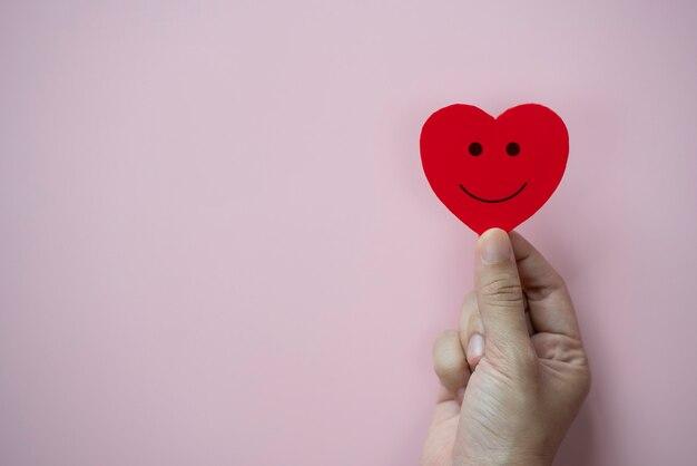 Mains tenant un coeur rouge avec une icône de visage souriant sur fond rose pastel