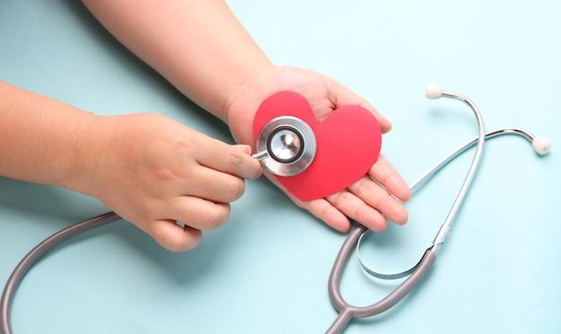 Mains tenant coeur rouge papier avec stéthoscope sur bleu.