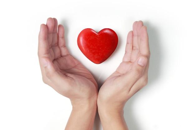 Mains tenant coeur rouge, santé cardiaque et concepts de don