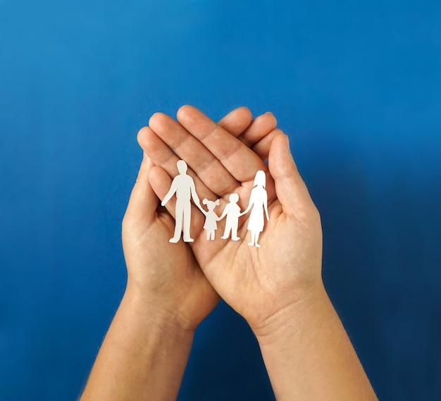 Mains tenant la découpe de la famille de papier, concept de distanciation sociale, covid19 sur le fond de couleur bleue, protection de la famille