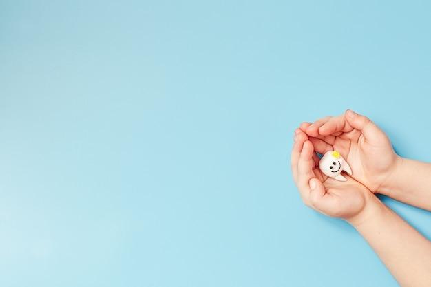 Mains tenant une dent de sourire, soins de santé, amour, dentiste de famille, journée mondiale des dents, journée mondiale de la santé, du bien-être,
