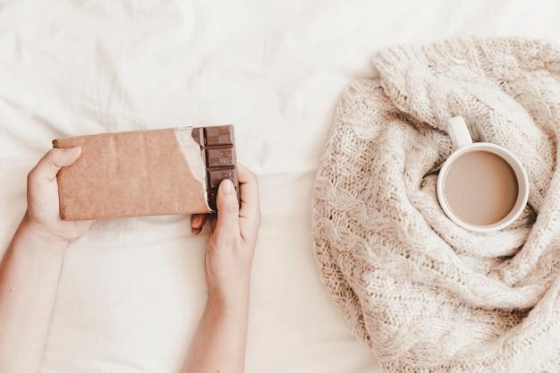 Mains tenant du chocolat près d'une tasse de boisson chaude dans un plaid sur un drap de lit