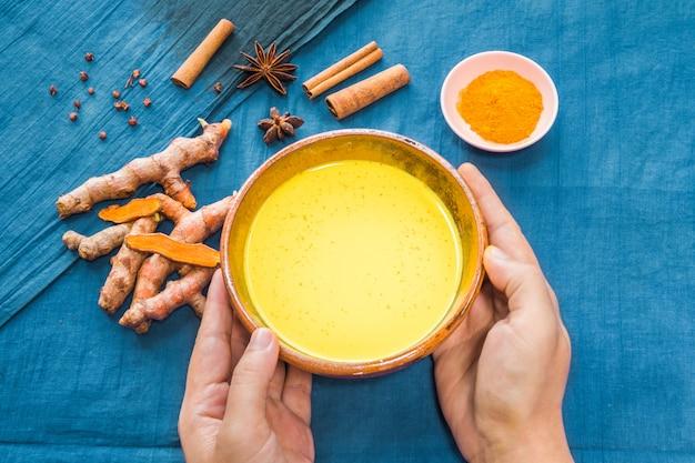 Mains tenant du lait de curcuma avec des ingrédients sur fond bleu