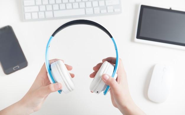 Mains tenant des écouteurs au bureau. écouter de la musique