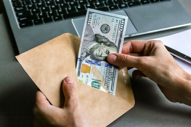 Mains tenant une enveloppe avec un billet de cent dollars, clavier d'ordinateur portable en arrière-plan.