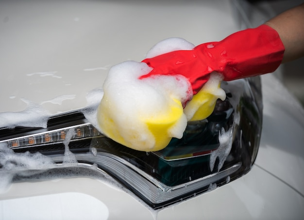 Mains tenant une éponge pour laver la voiture