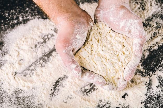 Mains tenant de la farine de blé blanche