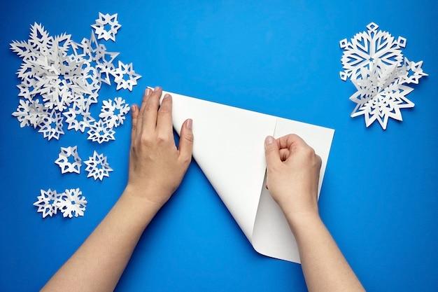 Mains tenant une feuille de papier blanc pour faire des flocons de neige