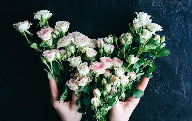 Mains tenant des fleurs sur fond noir. bouquet de roses. pose à plat parfaite avec des pétales. carte postale de vacances de mères heureuses. salutation de la journée internationale de la femme. idée d'anniversaire pour la publicité ou la promotion.