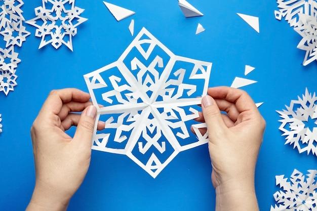 Mains tenant un flocon de papier découpé blanc sur une surface bleue