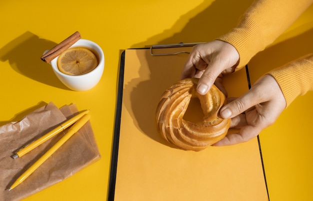 Mains tenant un gâteau près d'une tasse de thé ou de vin chaud et feuille de cv