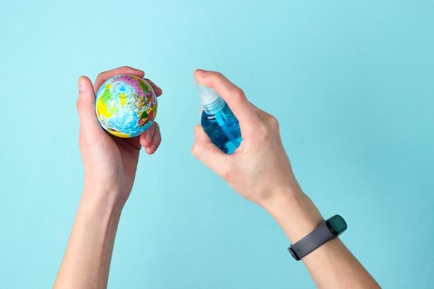 Mains tenant un globe et désinfecté avec un antiseptique sur bleu