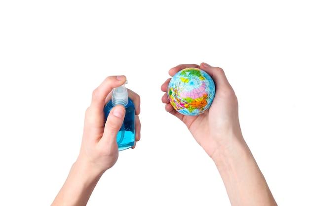 Mains tenant un globe et désinfecté avec un antiseptique isolé sur blanc