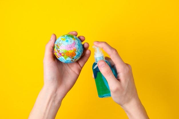 Mains tenant un globe et désinfecté avec un antiseptique sur un jaune