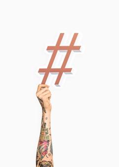 Mains tenant une icône de hashtag