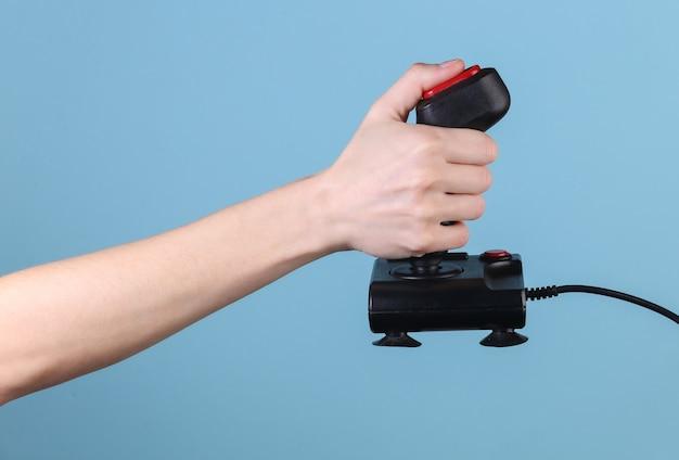 Mains tenant le joystick rétro sur fond bleu. vieux jeux. vague rétro des années 80