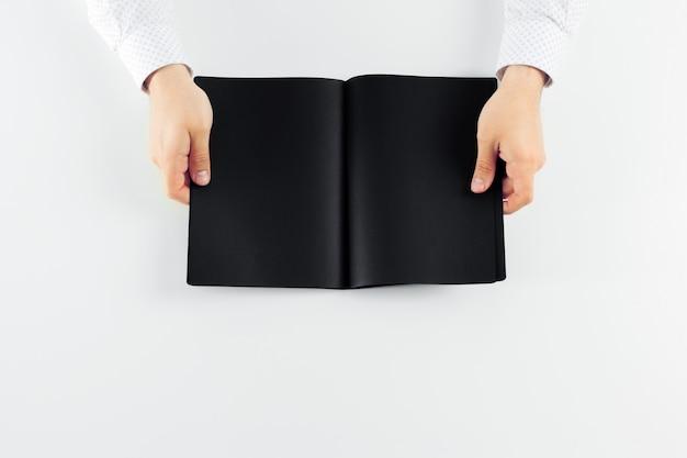 Mains tenant un livre blanc ouvert avec des pages noires