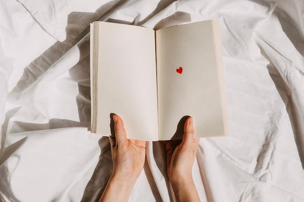 Mains tenant un livre blanc ouvert avec un petit coeur rouge