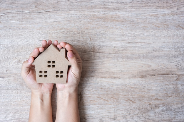 Mains tenant la maison modèle sur fond de table en bois avec espace de copie.