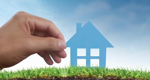 Mains tenant la maison de papier, la maison familiale et le concept d'assurance protégeant