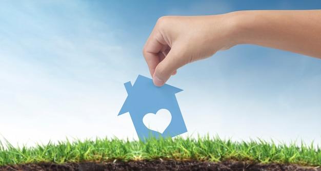 Mains tenant la maison de papier, la maison familiale et la protection du concept d'assurance