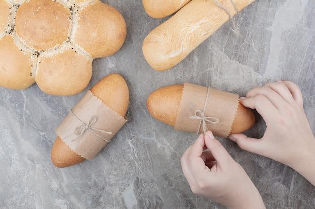 Mains tenant un mini pain sur une surface en marbre