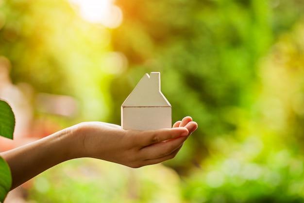 Mains tenant le modèle de maison en bois. achat d'un nouveau concept d'assurance habitation et habitation.