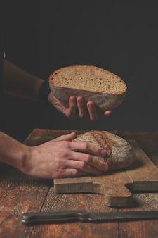 Mains tenant la moitié du pain sur un fond en bois foncé