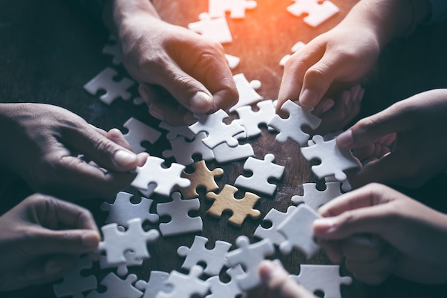 Mains tenant le morceau de puzzle blanc sur fond noir