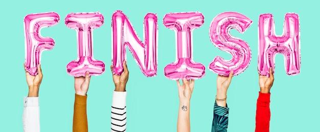 Mains tenant le mot d'arrivée en lettres de ballon