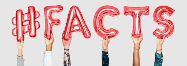 Mains tenant le mot #facts en lettres en ballon